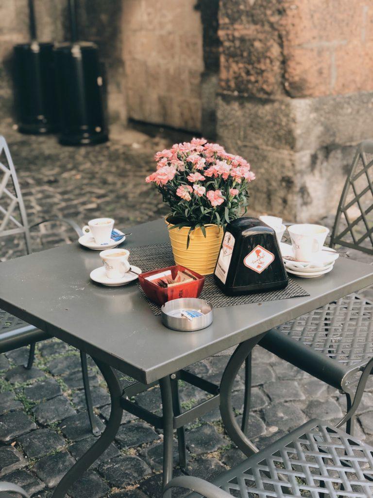 цветы и чашки кофе на столике уличного кафе